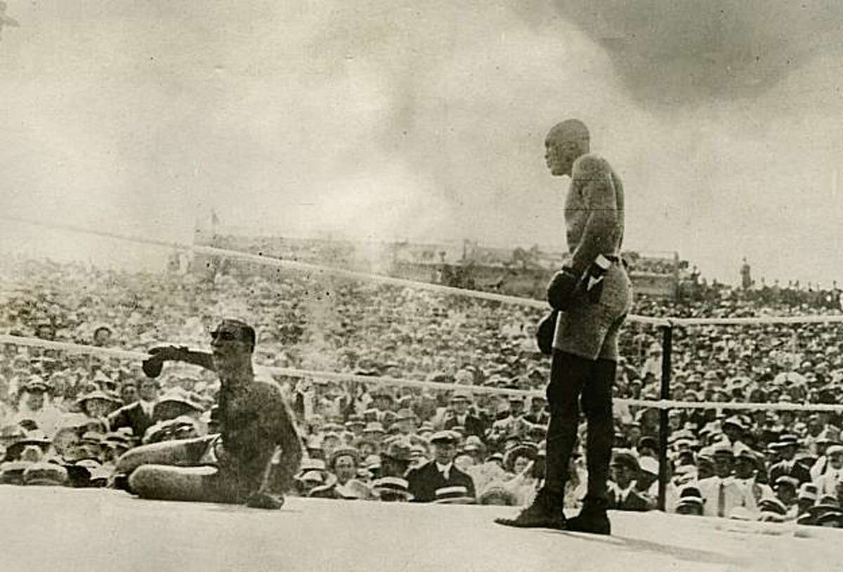 In this photo taken July 4, 1910 and provided by the Nevada Historical Society, Jack Johnson, right, knocks out Jim Jeffries in Reno Nevada. A century ago Johnson reached the pinnacle of his career when he defeated Jeffries in what was billed as the