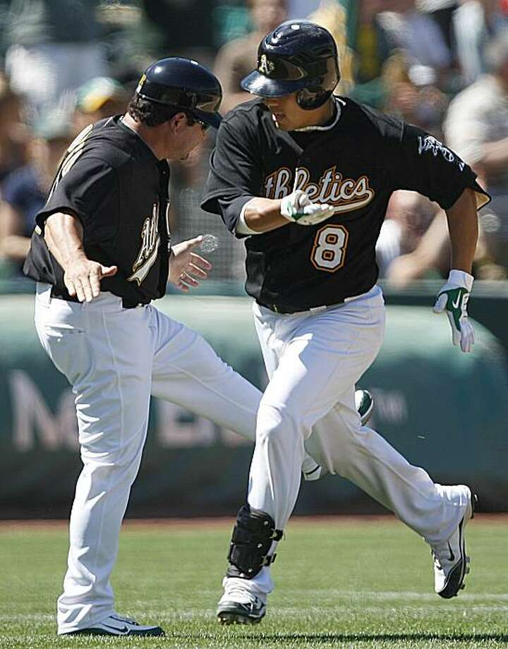 Oakland Athletics' Kurt Suzuki (8) is congratulated as he passes third base by coach Mike Gallego after Suzuki hit the game winning home run during the eighth inning of an inteerleague baseball game Sunday, June 27, 2010, in Oakland, Calif. Photo: Ben Margot, AP
