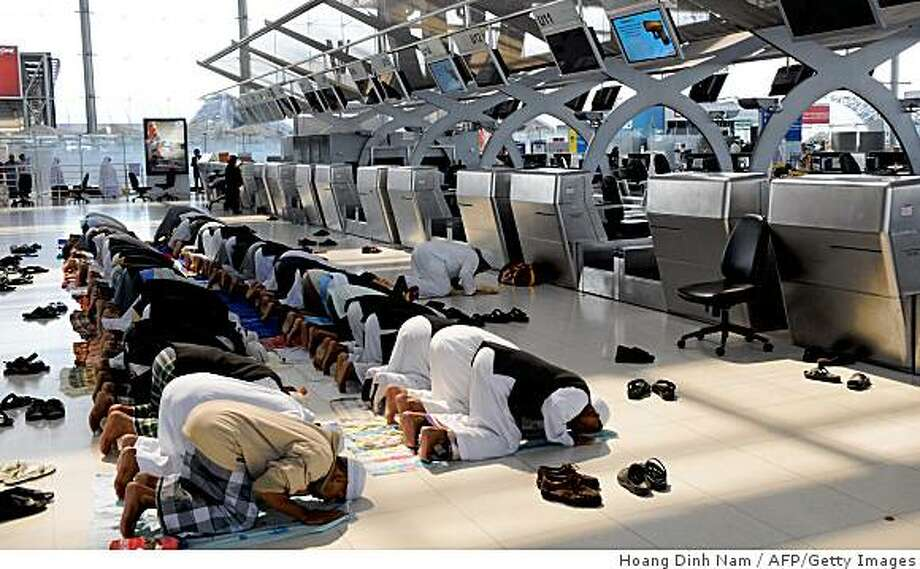 Stranded Thai Hajj pilgrims from Southern Thailand pray in front of check-in counters at the Suvarnabhumi airport in Bangkok on November 28, 2008. Thailand's embattled premier Somchai Wongsawat November 28 declared a state of emergency at Bangkok's main airports, seeking to clear them of protesters as the country's political crisis set off rumours of a coup. AFP PHOTO/HOANG DINH Nam (Photo credit should read HOANG DINH NAM/AFP/Getty Images) Photo: Hoang Dinh Nam, AFP/Getty Images