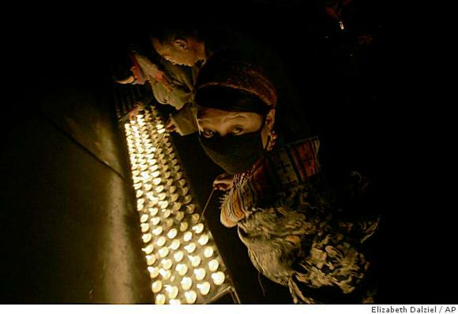 "Tibetan worshipers light candles in front of the monastery in Xiahe, China, Monday, Nov. 24, 2008. The Dalai Lama struck a pessimistic note, calling the next 20 years a period of ""great danger"" for Tibet, a seeming reference to Tibetans's ability to persevere and, at 73, his ability to live on and remain a rallying point. (AP Photo/ Elizabeth Dalziel) Photo: Elizabeth Dalziel, AP"