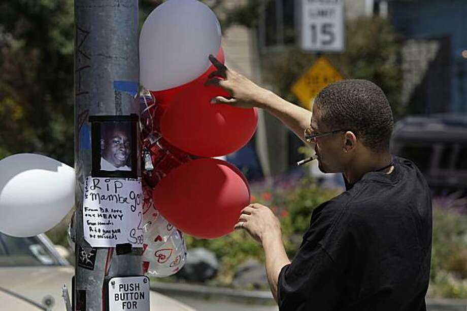 Surre Smith of San Francisco, holds back the balloons to look at a photo and read a message at a memorial at Quesada Avenue and Third Street for Stephen Powell who was shot and killed on Saturday at a weekend gay pride event in San Francisco, Calif. on Friday June 25, 2010.  Two men were shot around 8 p.m. Monday at a vigil for 19-year-old Stephen Powell. Photo: Lea Suzuki, The Chronicle
