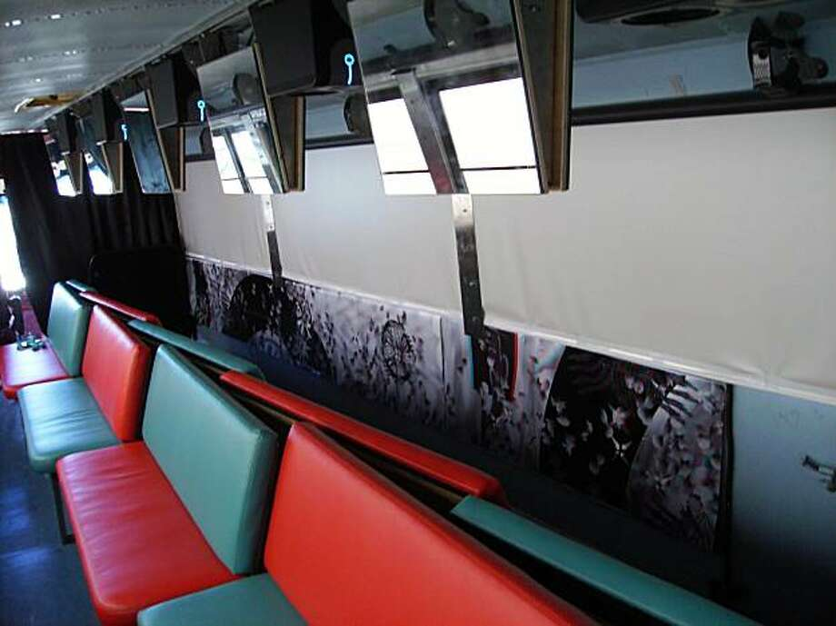"The interior of Antenna Theater's ""Magic Bus,"" with the seats facing the sides of the bus. The mirrors above the seats bounce projected film clips onto the roll-down screens that cover the windows. Photo: William Frohbose"