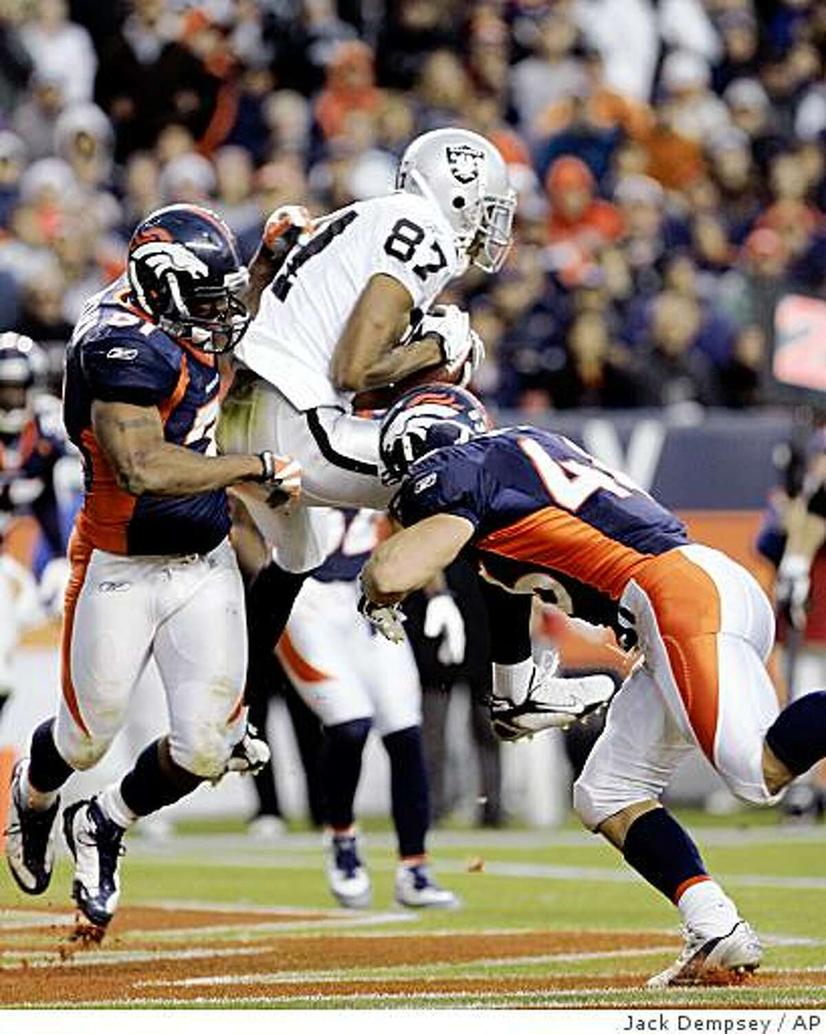 Oakland Raiders wide receiver Ashley Lelie (87) catches a touchdown pass against Denver Broncos linebacker Jamie Winborn (51) and Spencer Larsen (46) during the fourth quarter in Denver, Sunday, Nov. 23, 2008. The Raiders beat the Broncos 31-10.