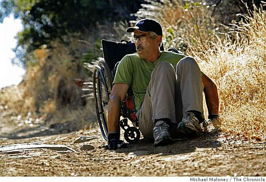 After slipping off his wheelchair, Bob Coomber of Livermore, Calif., continues up the steep trail pushing his wheelchair with his back.  The trail was just too steep, with no traction along this section of the Miwok Trail in Morgan Territory Regional Park near Livermore, Calif., on October 26, 2008. This was  Day 2 of a 4 day trek along the Diablo Regional Trail. Photo: Michael Maloney, The Chronicle