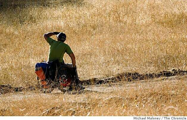 Coomber checks for wildlife as he heads up Miwok Trail among dry autumn grasses. Photo: Michael Maloney, The Chronicle