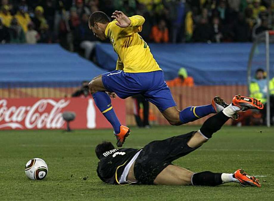 Brazil's Luis Fabiano, top, dribbles past Chile goalkeeper Claudio Bravo to score his side's second goal during the World Cup round of 16 soccer match between Brazil and Chile at Ellis Park Stadium in Johannesburg, South Africa, Monday, June 28, 2010. Photo: Alessandra Tarantino, AP