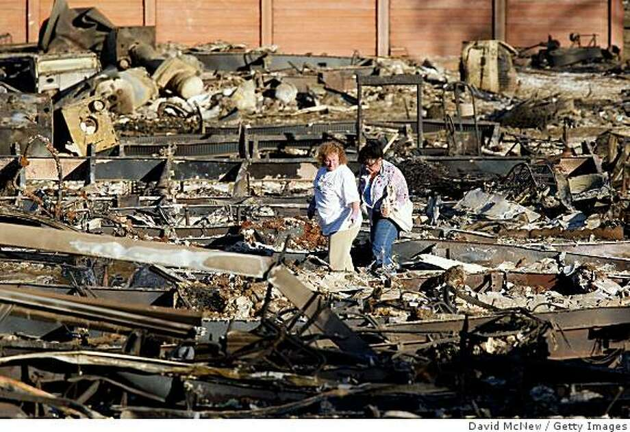 SYLMAR, CA - NOVEMBER 18:  Residents sift through the ashes of their homes at the Oakridge Mobile Home Park November 18, 2008 in Sylmar, California. Wildfire destroyed 480 modular homes in the pre-dawn darkness as 70-mile-per-hour winds blew into the community. The 11,207-acre Sayre Fire, previously called the Sylmar Fire, has burned 630 structures and is 70 percent contained. The Santa Ana winds that stoked a series of destructive wildfires across Southern California have dissipated, allowing firefighters to gain the upper hand. The firestorms prompted President Bush to issue a major disaster declaration today for Southern California making federal funding available for residents who lost homes or suffered other losses in the fires, which have destroyed about 1,000 homes.  (Photo by David McNew/Getty Images) Photo: David McNew, Getty Images