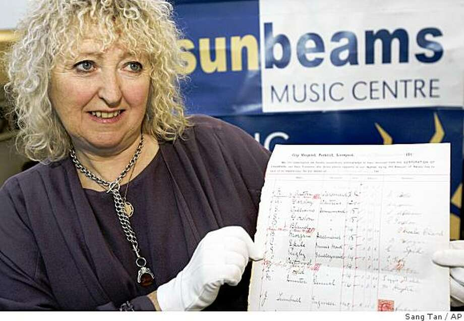 Annie Mawson, Founder and Chief Executive of Sunbeams Music Trust charity, poses with a page from a 1911 Corporation of Liverpool accounts book with an entry for Eleanor Rigby, a scullery maid, in London, Tuesday, Nov. 25, 2008. The only known documentation of Eleanor Rigby, sent to the Sunbeams Trust charity without explanation by Beatles member Paul McCartney, and said to be the inspiration behind one of their most-loved songs, is to be auctioned by The Fame Bureau, with an estimated price of GBP500,000 (USD758,000; euro 586,000). (AP Photo/Sang Tan) Photo: Sang Tan, AP
