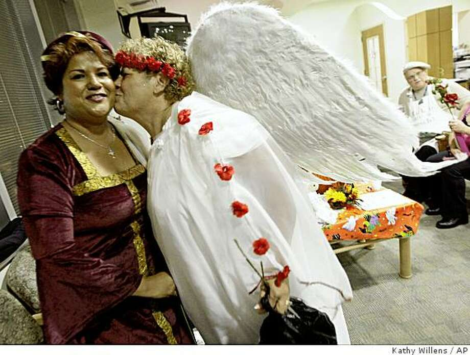 Lung cancer survivor Indrouti Zaman, left, gets a kiss on the cheek from breast cancer survivor Luz Rodriguez, dressed in a Halloween costume, during a laughter therapy session at Montefiore-Einstein Cancer Center in New York, Tuesday, Oct. 28, 2008. Patients meet regularly with an oncology social worker to tell amusing stories and off-color jokes. (AP Photo/Kathy Willens) Photo: Kathy Willens, AP
