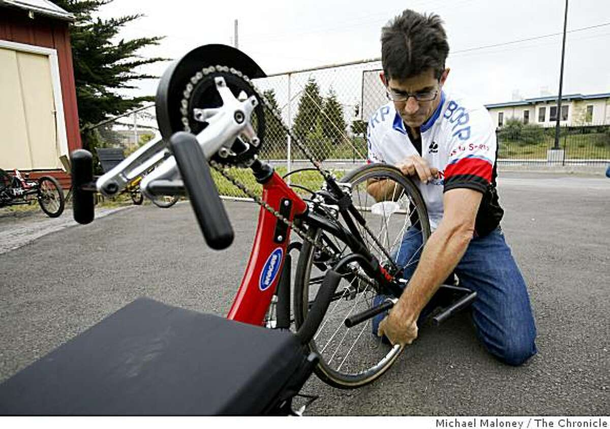 Greg Milano, Bay Area Outreach & Recreation Program (BORP) Cycling Coordinator adjusts the foot rests of a three-wheeled hand-crank bike.