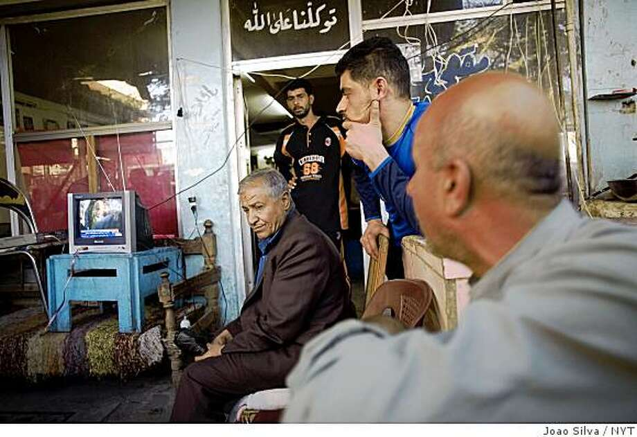 (NYT50) BAGHDAD, Iraq -- Nov. 27, 2008 -- IRAQ -- Iraqis gathered at a tea house in the Karada neighborhood of Baghdad, Iraq, where they watched a parliament in session on television on Thursday, Nov. 27, 2008. With a substantial majority, the Iraqi Parliament ratified on Thursday a sweeping security agreement that sets the course for an end to the United States role in the war and marks the beginning of a new relationship between the countries. The pact, which still must be approved by Iraq's three-person presidency council, a move expected in the next few days, sets the end of 2011 as the date by which the last American troops must leave the country. (Joao Silva/The New York Times) Photo: Joao Silva, NYT