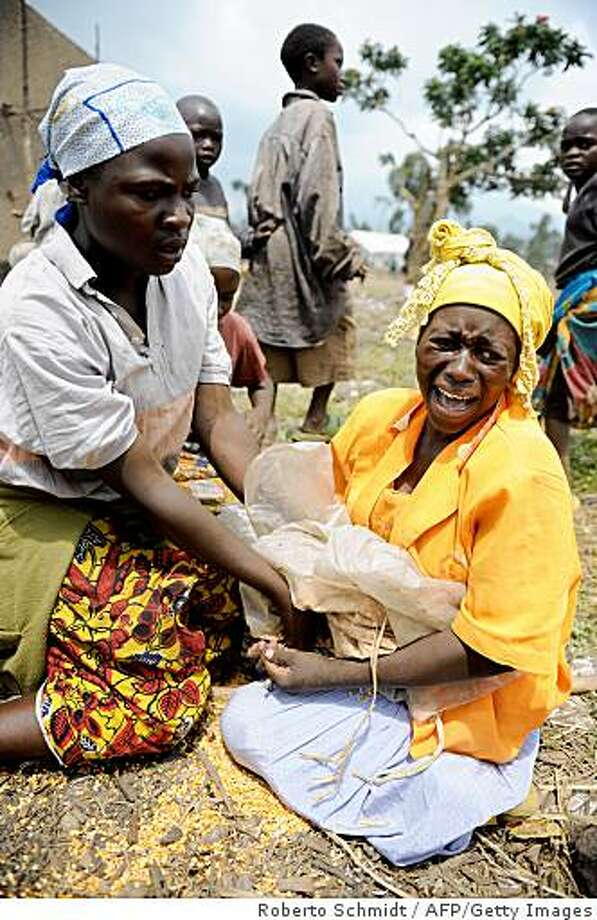 """A woman cries as she holds on to what is left of her portion of split peas after she was mobbed by a crowd near to a camp for Internally Displaced People (IDP) during a food aid distribution in Kibati on November 26, 2008. The UN's World Food Programme said yesterday it had distributed supplies to nearly 145,000 people displaced by recent fighting in the eastern Democratic Republic of Congo. It added that """"The security situation remains extremely unstable and the continuation of food aid distribution depends on getting escorts from MONUC (the UN mission in DR Congo) to certain regions,"""". AFP PHOTO/Roberto SCHMIDT (Photo credit should read ROBERTO SCHMIDT/AFP/Getty Images) Photo: Roberto Schmidt, AFP/Getty Images"""