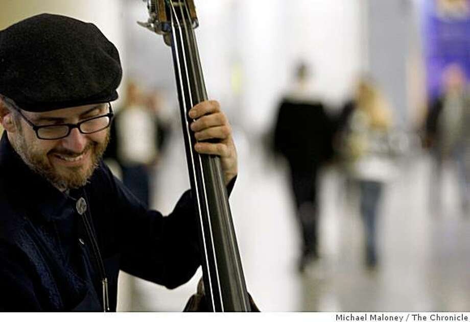 Bass player Devin Hoff of the Faye Carol quartet play jazz and blues to hurried holiday travelers at San Francisco International Airport in a series of concerts called 'You Are Hear at SFO'. The event on Wednesday, November 26, 2008 is the brainchild of local musician Marc Capelle. Photo: Michael Maloney, The Chronicle