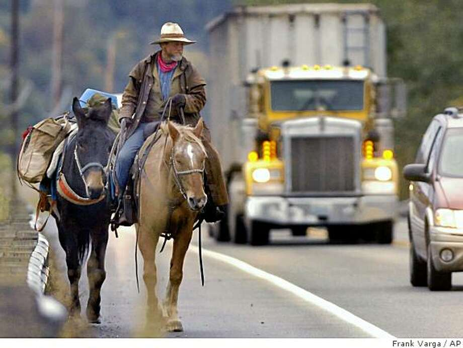 **ADVANCED FOR RELEASE NOV. 17** Mark Ryan, of Kingfisher, Okla,. makes his way north on HW 530, south of Conway, Wash., Thursday, Nov. 13, 2008. Ryan, his horse and a packmule, started out from Oklahoma for Ferndale, WA, on June 2nd  to visit a friend. Ryan said he always asks permission to camp on private property every night and usually gets it. Ryan's horse is on its sixth set of horseshoes and his mule on its third. (AP Photo/Frank Varga,  Skagit Valley Herald) Photo: Frank Varga, AP