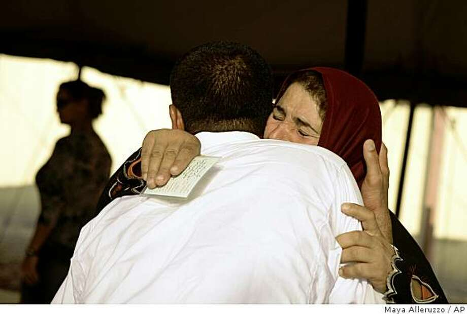 A woman embraces her husband, who is held at the U.S. detention facility at Camp Cropper in Baghdad, Iraq during a visiting day on Monday, Nov. 10, 2008. The U.S. military is rushing to collect evidence against some 5,000 detainees deemed to be dangerous _ including suspected members of al-Qaida in Iraq _ in case it loses the right to hold prisoners indefinitely without charge at the end of the year. (AP Photo/Maya Alleruzzo) Photo: Maya Alleruzzo, AP