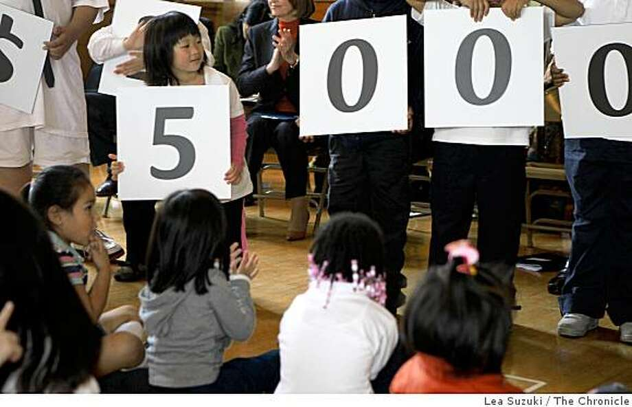 Visitation Valley Elementary School kindergardener Jacklyn Lam (left-holding number 5) steps forward to take a look at the numbers being held up as Visitation Valley Elementary School students hold up numbers showing the amount a Milken Family Foundation National Educator Award recipient will receive shortly before the Milken Family Foundation National Educator Awards surprised Mindy Yip, a Visitation Valley Elementary School teacher, with a $25,000 prize at the Visitation Valley Elementary School  in San Francisco, Calif. on Monday, November 23, 2008. Photo: Lea Suzuki, The Chronicle