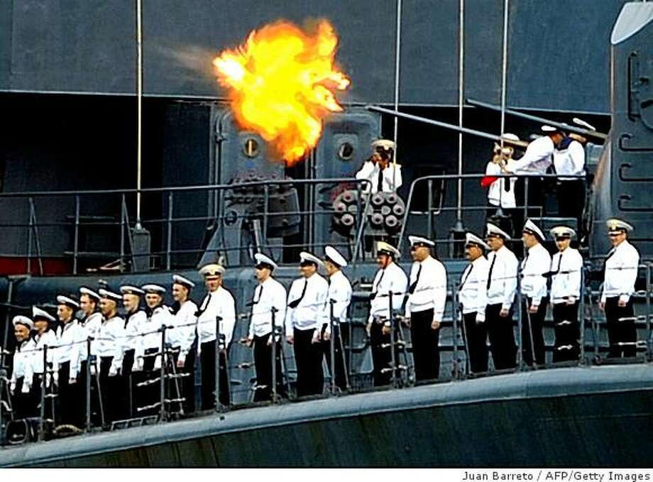 Russian Udaloy-class Admiral Chabanenko anti-submarine vessel crewmen stand in attention on the deck as a salvo is fired in salutation, upon her arrival at the port of La Guaira, 30 km from Caracas, on November 25, 2008. A Russian naval squadron led by Northern Fleet's flagship Pyotr Veliky (Peter the Great) nuclear-powered missile cruiser, arrived in Venezuela to conduct a joint exercise with the Venezuelan Navy. The combined exercise was agreed on July 2008, when Venezuelan President Hugo Chavez visited moscow. AFP PHOTO/Juan BARRETO (Photo credit should read JUAN BARRETO/AFP/Getty Images) Photo: Juan Barreto, AFP/Getty Images