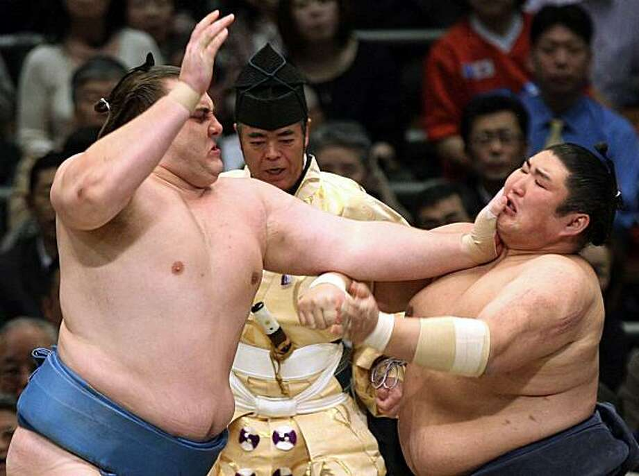 "Estonian sumo wrestler Baruto (L) pushes ""ozeki"" ranked wrestler Kotomitsuki (R) of Japan during their bout on the final day of the 15-day Spring Grand Sumo Tournament in Osaka, western Japan on March 28, 2010. Baruto beat Kotmitsuki to finish second in the tournament with a 14-1 overall record after ""yokozuna"" or grand champion Hakuho of Mongolia, who won the tournament with a perfect 15-0 record.  With the strong 14-1 record, Baruto wrapped up a successful push for promotion to ""ozeki"", or champion, the second highest sumo rank, and will become only the second European after ozeki-ranked wrestler Kotooshu of Bulgaria.    AFP PHOTO / JIJI PRESS (Photo credit should read JIJI PRESS/AFP/Getty Images) Photo: Jiji Press/AFP, Getty Images"