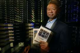 Sai Wai Fu, founder, president and CEO of YesVideo, at his company in Santa Clara, Calif., on Wednesday, June 9, 2010.  Behind him is the new memory safe that archives transfers for an annual fee.