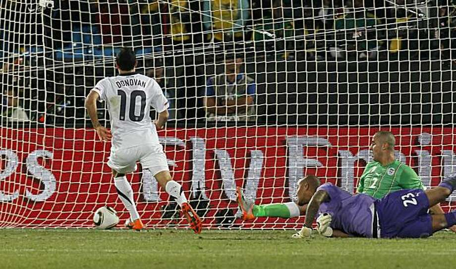 United States' Landon Donovan, left, scores a goal past Algeria goalkeeper Rais M'Bolhi, front right, and Algeria's Madjid Bougherra, back right, during the World Cup group C soccer match between the United States and Algeria at the Loftus Versfeld Stadium in Pretoria, South Africa, Wednesday, June 23, 2010. Photo: Eugene Hoshiko, AP