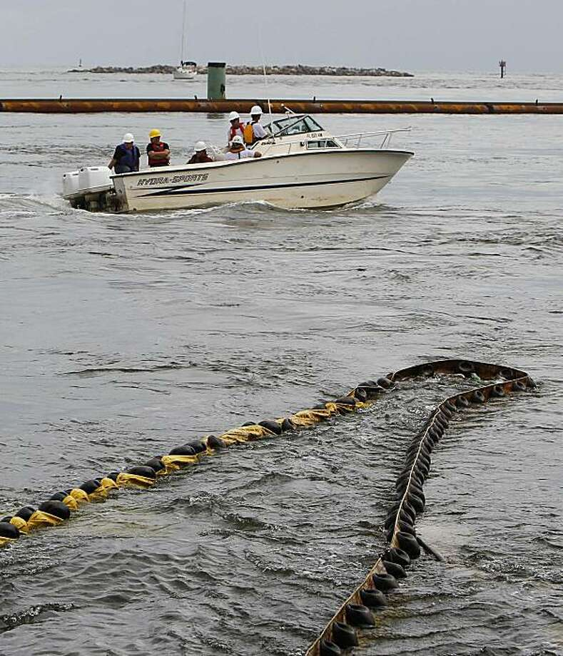 A work boat navigates past oil containment booms in the Perdido Pass in Orange Beach, Ala., Tuesday, June 22, 2010. Authorities are attempting to boom the pass which has one of the strongest currents along the Gulf coast in an effort to defend against oilfrom the Deepwater Horizon disaster. Photo: Dave Martin, AP