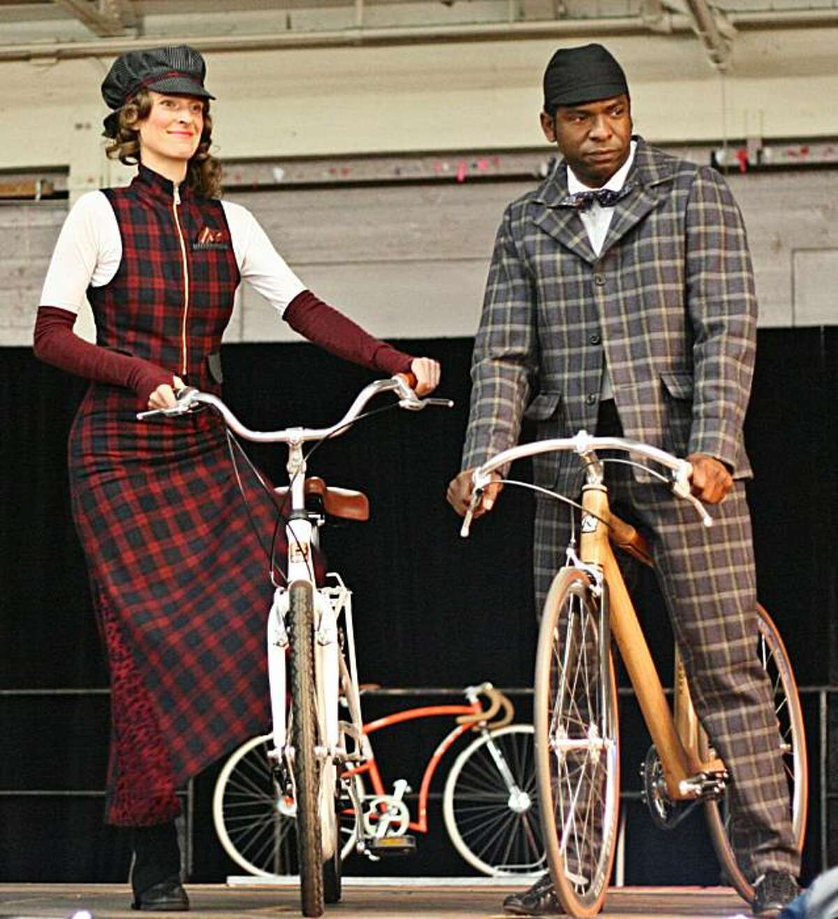 Bridget Frederick, a designer and the manager of recycled products at B. Spoke Tailor, and Eddie Johnson, model at the SF Bike Expo/Momentum Magazine Fashion show in 2009 at the Cow Palace. The suit is a Dashing Tweeds Lumatwill. The skirt, vest and hat are English tartans. The outfit was styled by Gwen Lutz.