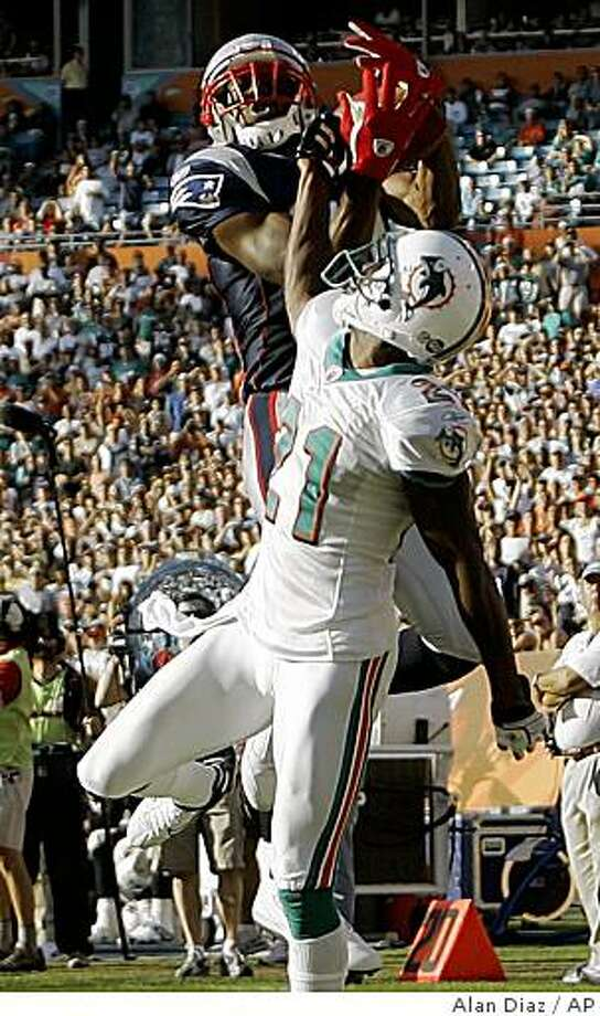 New England Patriots wide receiver Randy Moss, top, catches a touchdown pass as Miami Dolphins cornerback Andre Goodman attempts the block during the fourth quarter of an NFL football game Sunday, Nov. 23, 2008 in Miami. The Patriots defeated the Dolphins 48-28. (AP Photo/Alan Diaz) Photo: Alan Diaz, AP