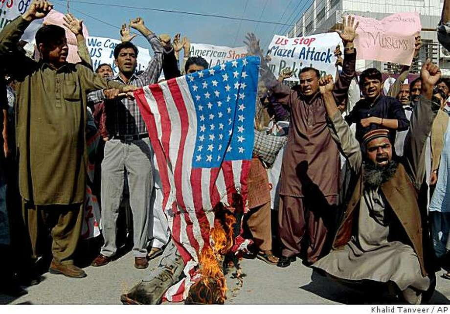 Pakistani traders chant slogans next to a burning U.S. flag during a rally to condemn the U.S. missile strikes in country's tribal areas, Sunday, Nov. 23, 2008, in Multan, Pakistan. Pakistanis protested an American missile strike that killed a top British militant suspect near the Afghan border, saying their Western-allied government must stop the attacks. (AP Photo/Khalid Tanveer) Photo: Khalid Tanveer, AP