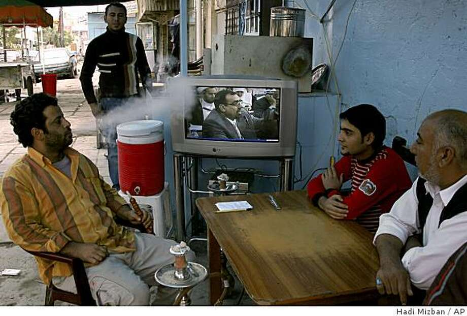 Iraqis watch a session of parliament as it debates a U.S.-Iraqi security pact on television in Baghdad, Iraq, Saturday, Nov. 22, 2008. Saturday's session is being shown live on national television and has been orderly so far. Chaotic scenes marred debate earlier this week when opposition lawmakers loyal to Shiite leader Muqtada al-Sadr disrupted the proceedings. (AP Photo/Hadi Mizban) Photo: Hadi Mizban, AP