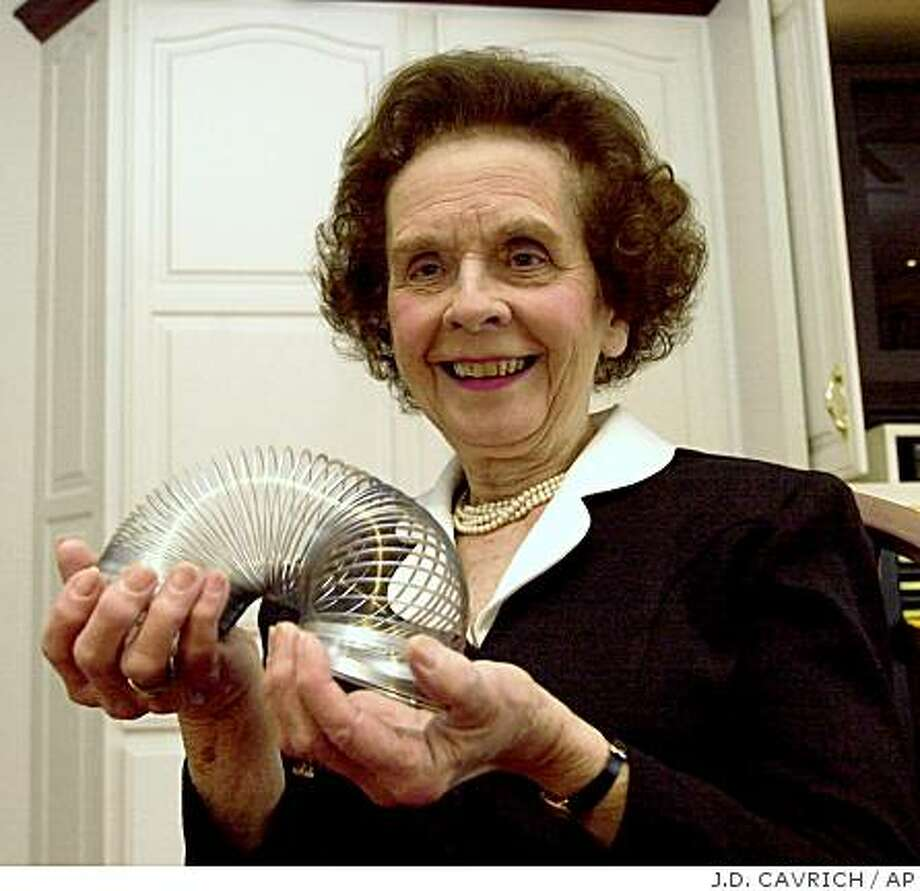 ** FILE ** In this Jan. 18, 2001 file photo, Betty James, retired  president of James Industries, plays with a toy Slinky that made the family company famous  in Hollidaysburg, Pa. James, who co-founded the company that made the Slinky and beat the odds as a single mother in the late 1950s to become a successful executive, has died. She was 90.  She died Thursday Nov. 20, 2008, said a spokeswoman for the Hospital of the University of Pennsylvania in Philadelphia. (AP Photo/The Altoona Mirror, J.D. Cavrich, File) Photo: J.D. CAVRICH, AP