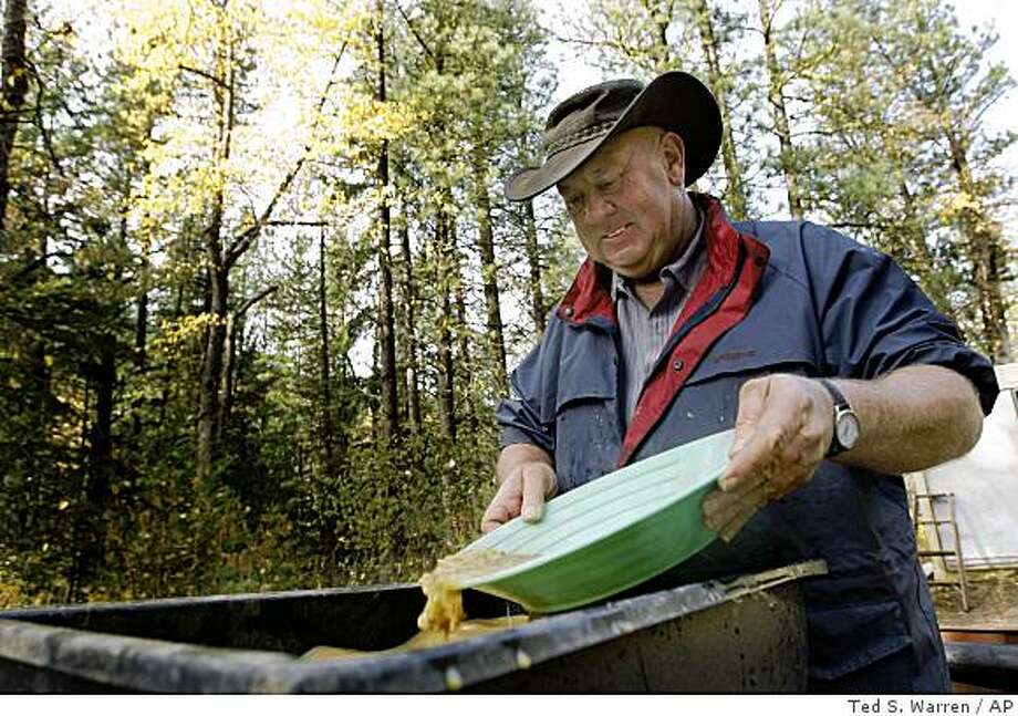 Ed Levesque pans for gold on his mining claim land Sunday, Nov. 2, 2008, in near Liberty, Wash., Prospectors such as Levesque who dig or dredge for gold in certain creeks, streams and rivers are facing increased state regulations aimed at protecting fish and fish eggs during critical spawning periods. (AP Photo/Ted S. Warren) Photo: Ted S. Warren, AP