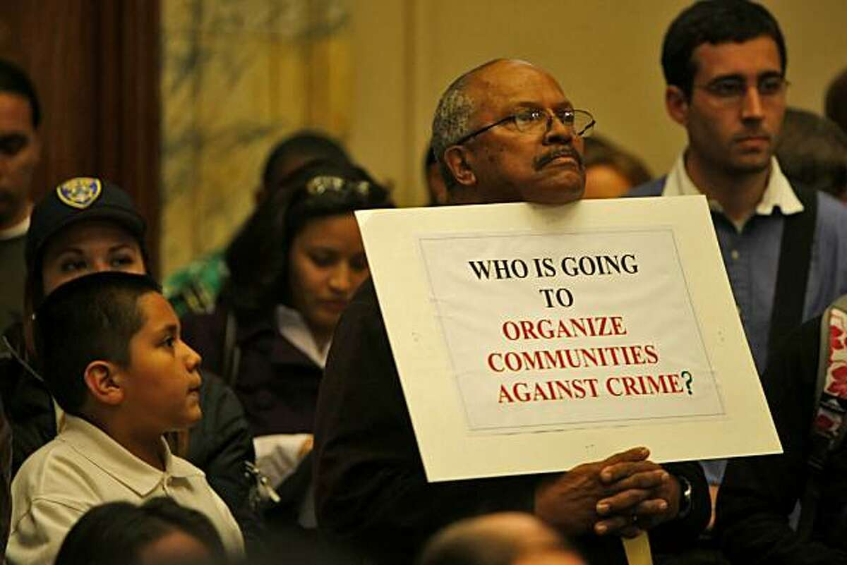 Don Smith holds up a sign during the town meeting as Mayor Ron Dellums addresses the Oakland City Council, Thursday June 24, 2010, at the Oakland City Hall in Oakland, Calif. More than 200 members of the community spoke to the council on a number of issues. Most on the issue of laying off the police officers.