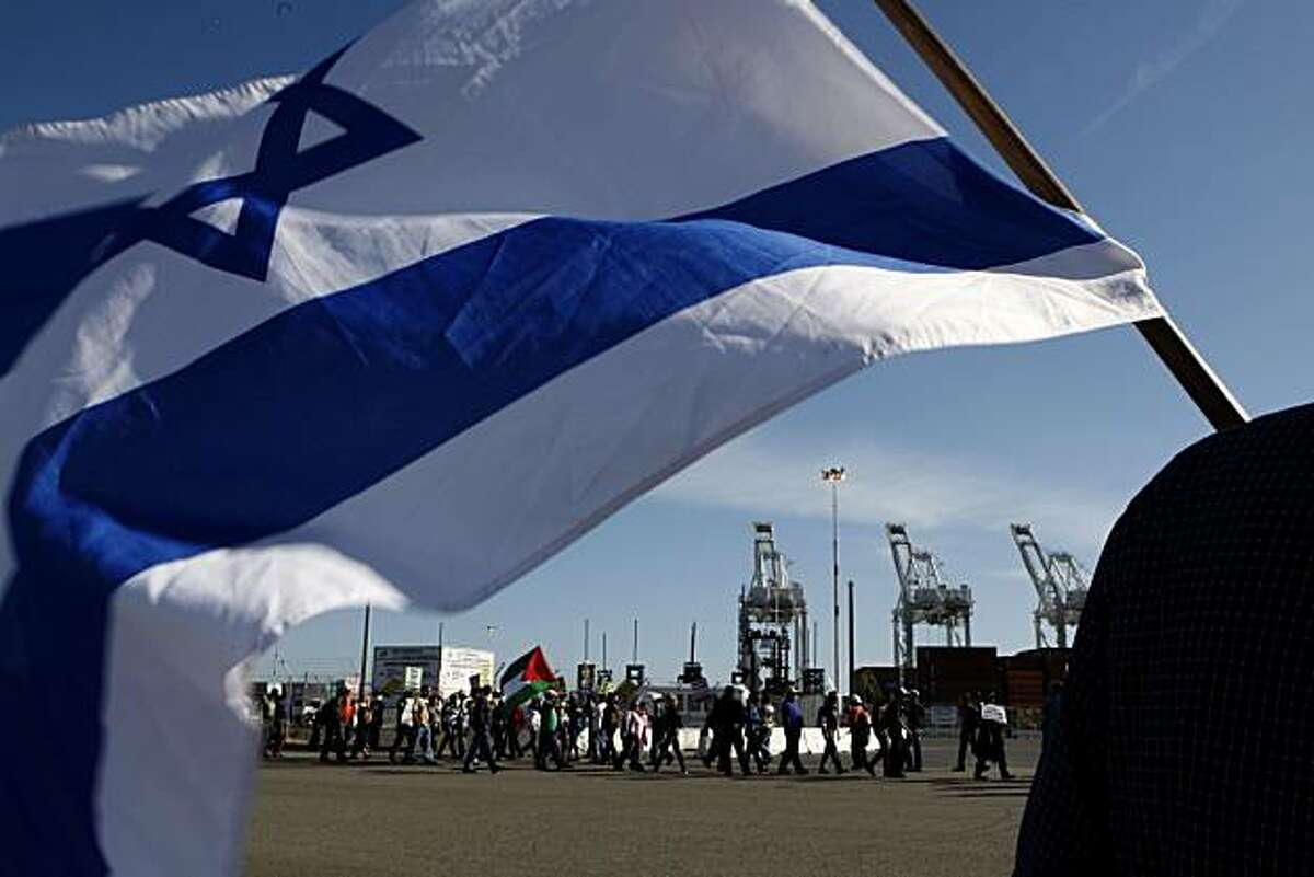 Marshall Schwartz of Oakland waves an Israeli flag across the road from pro-Palestinian supporters protesting the Israeli Zim Shipping Line at the Port of Oakland on Sunday.