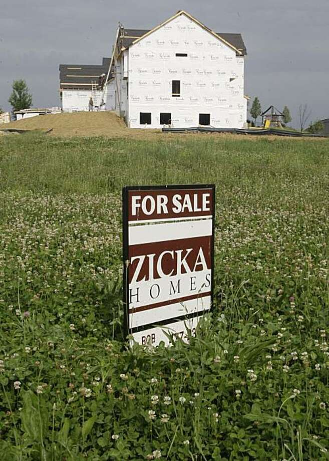 In this photo taken June 2, 2010, a for sale sign is posted in a lot next to a new home under construction in Cincinnati. Sales of new homes collapsed last month, sinking 33 percent to the lowest level on record as potential buyers stopped shopping for homes once they could no longer get government incentives. Photo: Al Behrman, AP