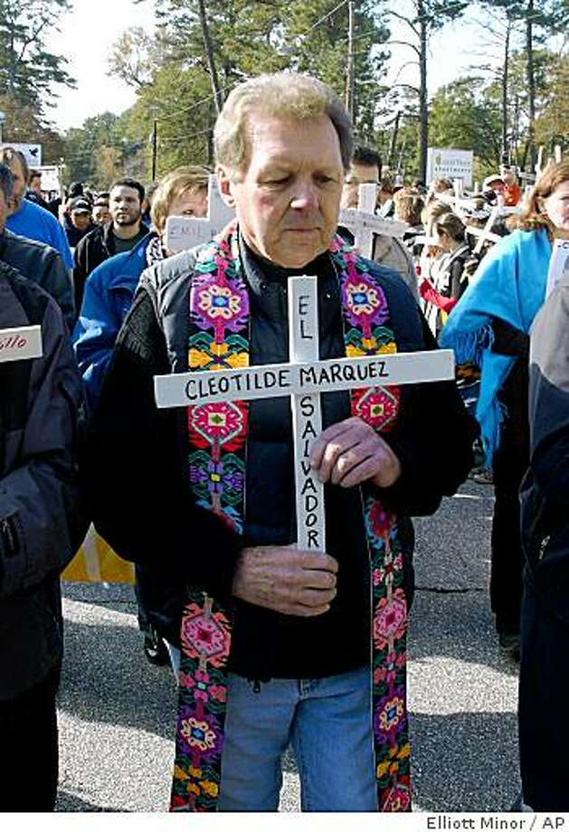 "Roy Bourgeois, founder of School of Americas Watch, leads a procession Sunday, Nov. 23, 2008 in Columbus, Ga., to honor victims of alleged human rights abuses in Latin America. Bourgeois, a Maryknoll priest who has been leading the demonstrations outside a gate to Fort Benning since 1990, said his supporters view president-elect Barack Obama as the ""president who stands for peace"" and will request a meeting with him. (AP Photo/ Elliott Minor) Photo: Elliott Minor, AP"