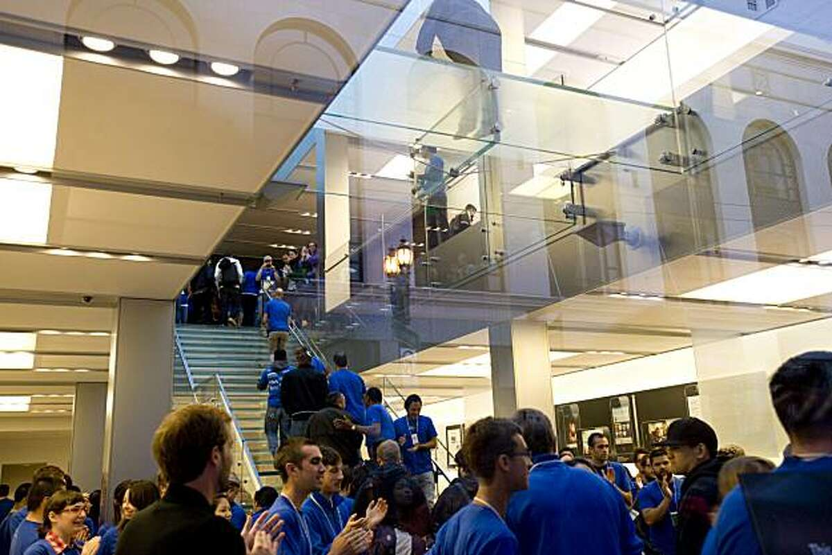 Upon the store opening at 7 a.m., the first guests hurry up the stairs to get their iPhone 4 as Apple employees cheer them on at the Apple store in San Francisco, Calif., on June 24, 2010, the day of the iPhone 4 debut.
