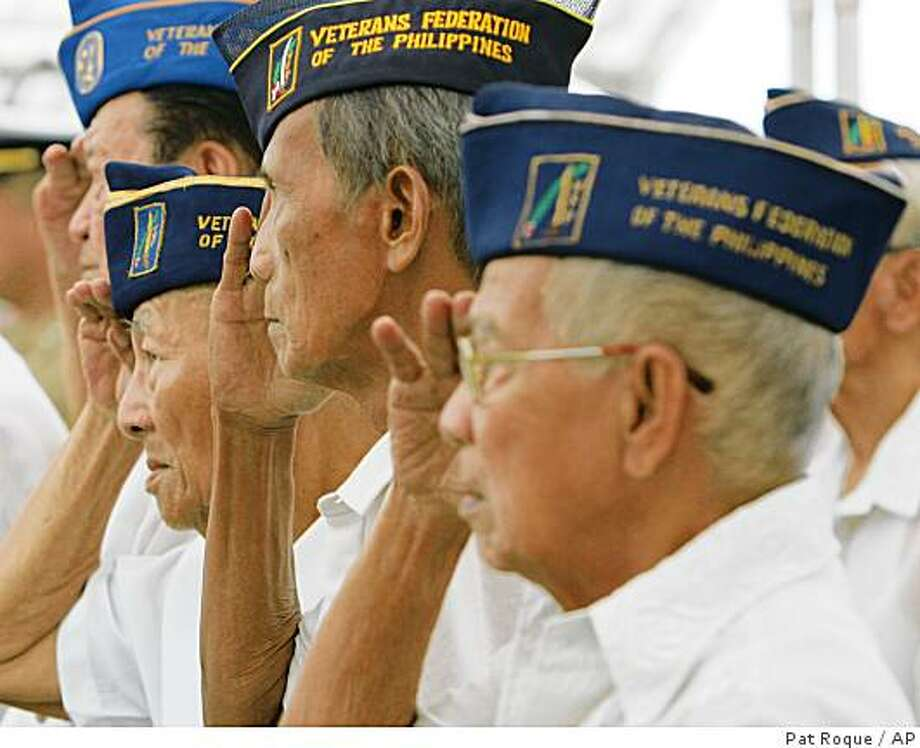 **APN ADVANCE FOR NOV 23**  A group of Filipino World War II veterans salute as the national anthem is played during the commemoration of Veterans Day Tuesday, Nov. 11, 2008 at the American Cemetery in suburban Taguig south of Manila. The event was held to honor Americans and Filipino veterans. The day was originally commemorated by Americans as Armistice Day to mark the end of World War I in 1918 but now held in honor of all those who fought with the United States in its wars ever since. (AP Photo/Pat Roque) Photo: Pat Roque, AP