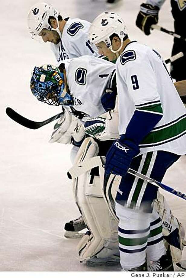 Vancouver Canucks goalie Roberto Luongo, center, is helped off the ice by teammates Ryan Kesler, rear, and Taylor Pyatt (9) after being injured in the first period of an NHL hockey game  against the Pittsburgh Penguins in Pittsburgh Saturday, Nov. 22, 2008. (AP Photo/Gene J. Puskar) Photo: Gene J. Puskar, AP
