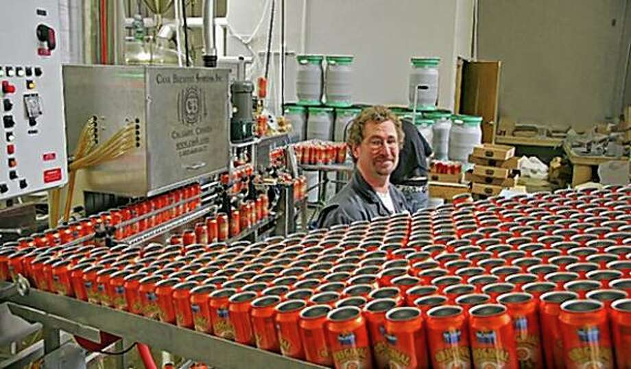 Dan Kahn, brewmaster at Buckbean Brewing Co. in Reno is surrounded by Orange cans about to be filled with Orange Blossom Ale. Reno now has several local brews. Photo: Mark S. Bacon