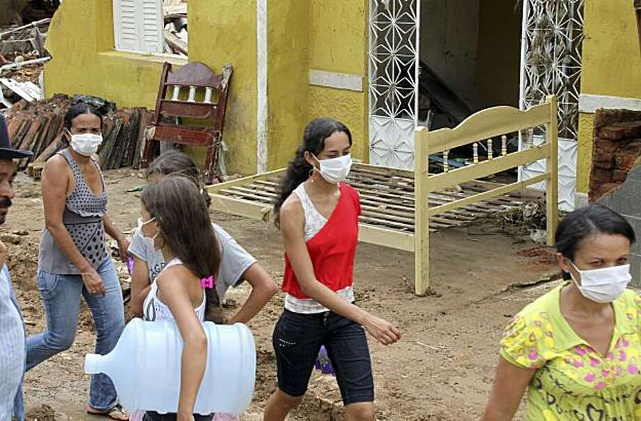 In this image released by the Alagoas state government, residents wear masks to protect from airborne diseases, in Santana do Mundau, Brazil, Tuesday, June 22, 2010. Brazilian officials are scrambling to get food and medical aid to flood victims in the nation's northeast, where at least 41 people have been reported dead and thousands forced to leave their homes. Photo: Adailson Calheiros, AP