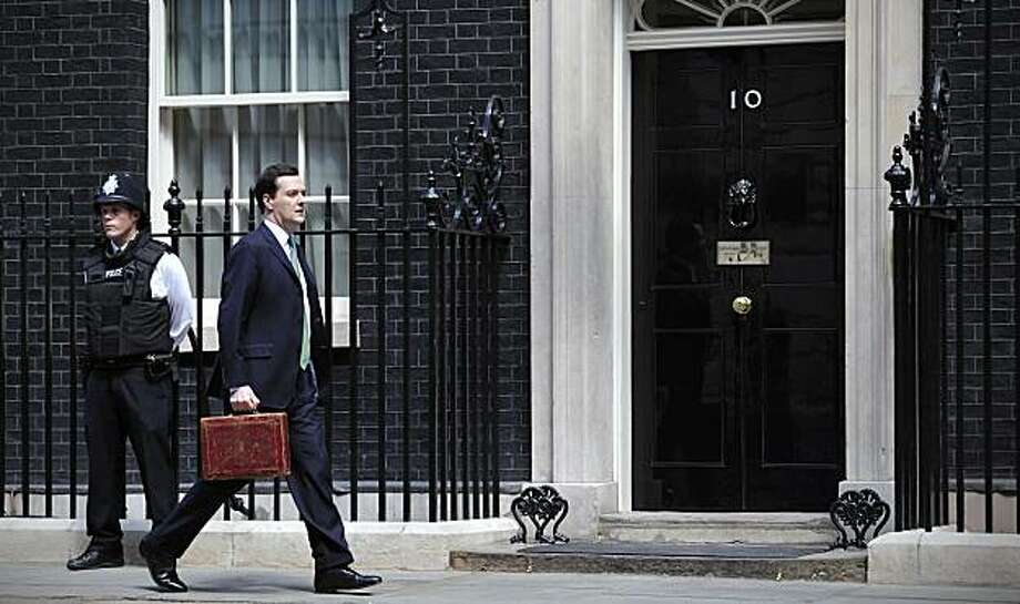 "British Chancellor of the Exchequer George Osborne (R) walks past the door of 10 Downing Street in London, on June 22, 2010, as he prepares to unveil an emergency budget to the House of Commons. Osborne pledged Tuesday to balance the books within five years, a spokesman said, shortly before he was to unveil an emergency austerity budget. ""My budget is tough but it will be fair,"" he said, cited by the official spokesman of Prime Minister David Cameron, whose Conservative party won May elections and formeda coalition with the third-placed Liberal Democrats. Photo: Carl Court, AFP/Getty Images"