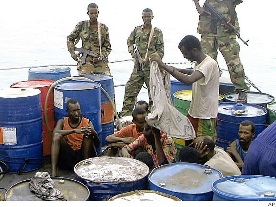 Armed Puntland police guard captured Somali pirates in Bassaso, Somalia, Friday, Nov. 21, 2008. Ministers of Puntland state, a self-declared autonomous area, told journalists that they have many Somali pirates in their detention centers. A multinational effort is being mobilized to provide security in the area to fight the pirates off Somalia,  involving the European Union, NATO countries, Russia, India and others nations. (AP Photo) Photo: AP