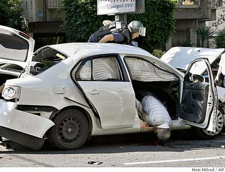"An Israeli police officer from the bomb unit examines a car as the body of man hangs out of the passenger side door after an explosion in Tel Aviv, Monday Nov. 17,  2008. A huge car explosion in central Tel Aviv killed one of Israel's top mafia kingpin's on Monday, raising the likelihood of an all-out mob war in Israel's underworld. Israeli media identified the dead man as Yaakov Alperon_known informally as ""Don Alperon"" _ but police would not confirm the report. (AP Photo/Moti Milrod) Photo: Moti Milrod, AP"