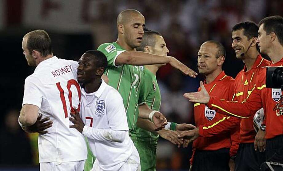 England's Aaron Lennon, second from left, pushes away Wayne Rooney, left, as Algeria's Madjid Bougherra, top, shakes hands with a linesman after the World Cup group C soccer match between England and Algeria in Cape Town, South Africa, Friday, June 18, 2010. Second from right, referee Ravshan Irmatov, of Uzbekistan. Photo: Julie Jacobson, AP