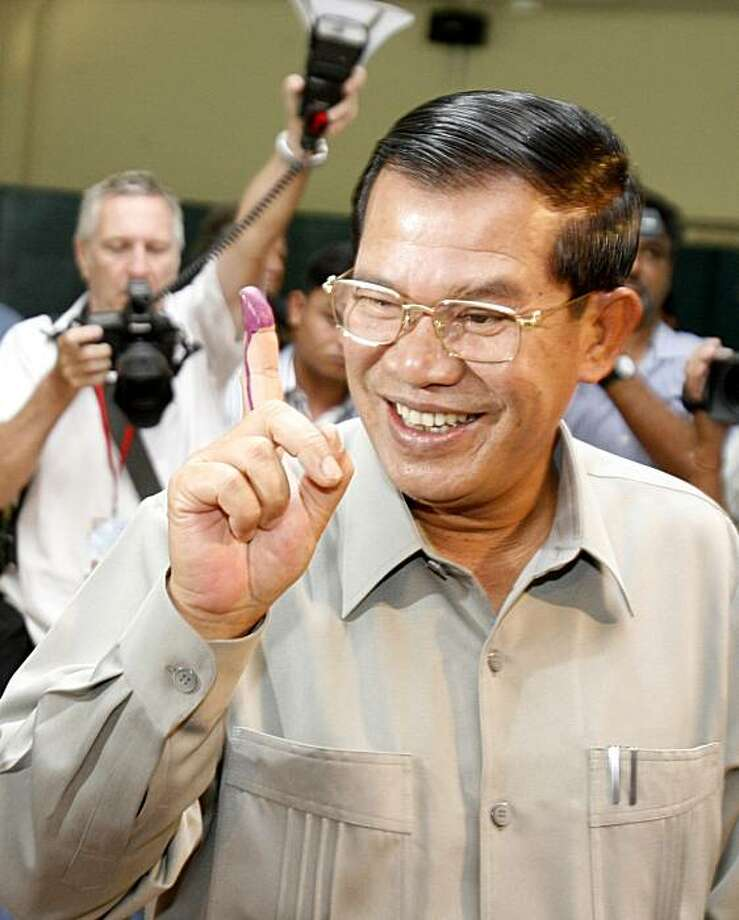Prime Minister Hun Sen shows off his finger tainted with purple ink after casting his ballot at a polling station in Takhmau, Kandal province, south of Phnom Penh, Cambodia, Sunday, July 27, 2008. Longtime Cambodian Prime Minister Hun Sen is widely expected to extend his 23-year tenure with a victory in Sunday's parliamentary elections, buoyed by a surge of nationalism amid a tense border dispute with neighboring Thailand. (AP Photo/Heng Sinith) Photo: Heng Sinith, AP