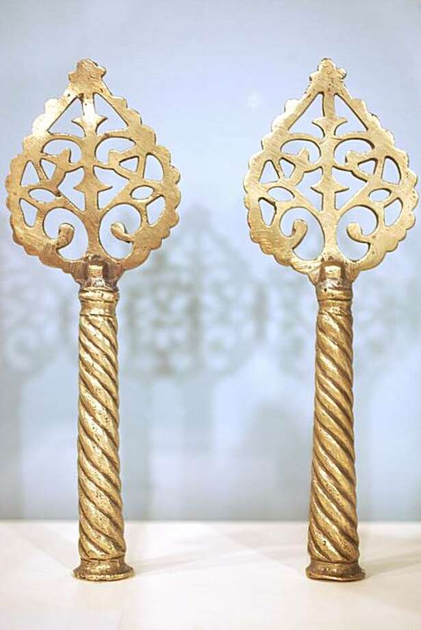 "Torah finials, Date unknown, Morocco, Brass, Anonymous gift 86.0.09     Torah finials,  or rimmonim,  ornament the staves on which the Torah scroll is rolled. The Hebrew word ""rimmon"" means pomegranate, a symbol of life and fertility. Sephardic rimmonim are often topped with a bud, fruit, or flower, identifying the Torah as a ""Tree of Life."" Photo: Lea Suzuki, The Chronicle"
