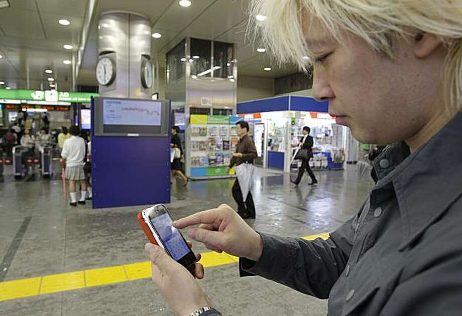 "In this June 14, 2010 photo, Daisuke Tsuda tweets with his mobile phone at a station in Tokyo. ""Japan is enjoying the richest and most varied form of Twitter usage as communication tool,"" says Tsuda, 36, a writer with more than 65,000 ""followers"" for histweets. ""It's playing out as a rediscovery of the Internet."" Photo: Koji Sasahara, AP"