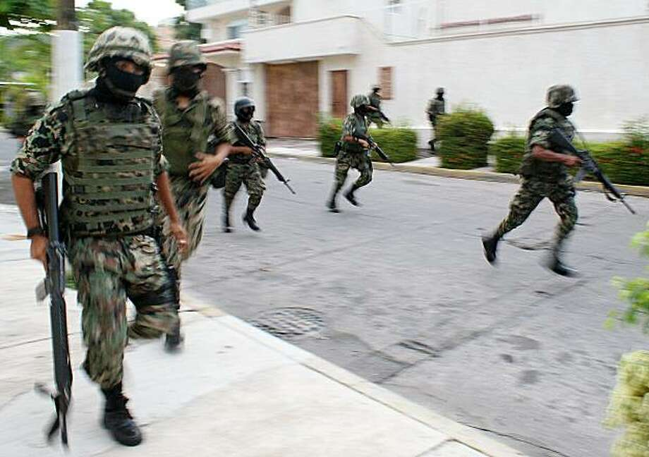 Mexican Navy marines run down a street after a gunbattle erupted in the Pacific resort city of Acapulco, Mexico Wednesday June 16, 2010. According to news bulletin released by the Mexican Navy, the marines came under fire as they approached a home they intended to inspect after they got an anonymous tip alerting suspicious activity in that home. Two people were detained. Photo: Bernandino Hernandez, AP