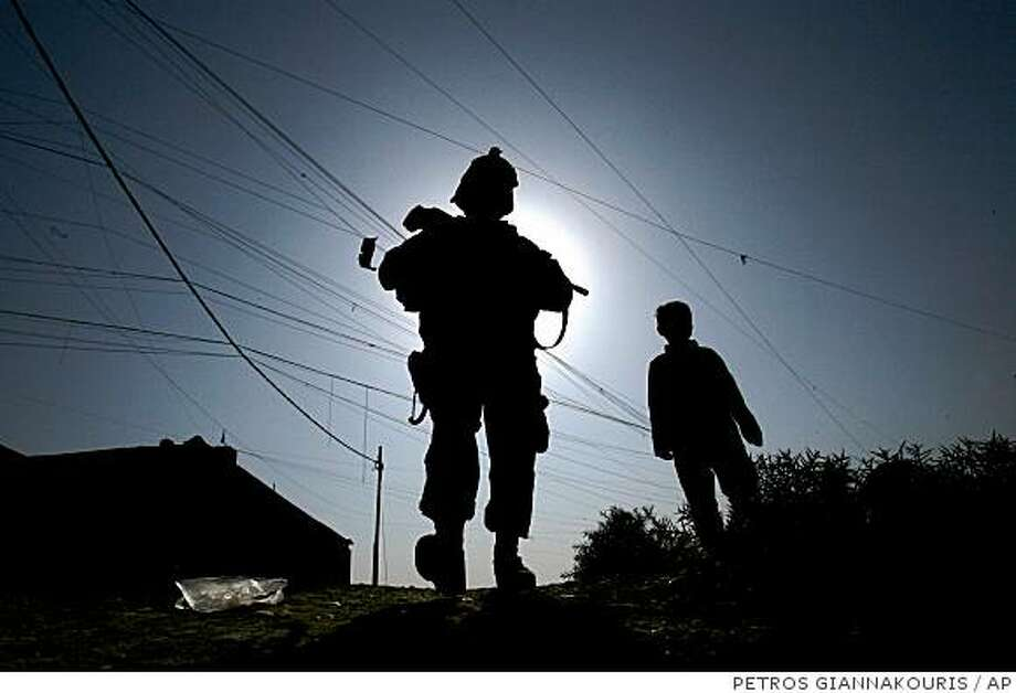 A U.S soldier of Lightning Troop, 3rd Squadron, 3rd Armored Cavalry Regiment, walks next to an Iraqi child  during a patrol in 17th Tammooz neighborhood, northwestern Mosul, 360 kilometers (225 miles) northwest of Baghdad, Iraq, on Tuesday, Nov. 18, 2008. (AP Photo/Petros Giannakouris) Photo: PETROS GIANNAKOURIS, AP