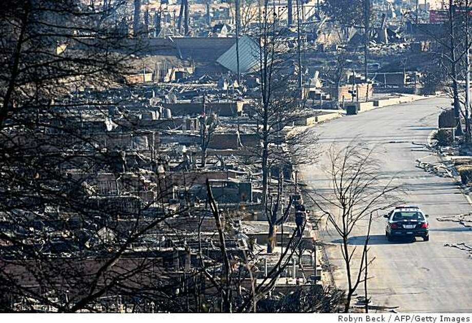 A police car patrols the wildfire-ravaged streets of the Oakridge Mobile Home Park as the search continues for the remains of people who may not have escaped the fire, in the Sylmar neighborhood of Los Angeles,California on November 17, 2008.  Hundreds of homes in the park were destroyed on November 15, 2008 by a wind-driven wildfire.  AFP PHOTO / Robyn BECK (Photo credit should read ROBYN BECK/AFP/Getty Images) Photo: Robyn Beck, AFP/Getty Images